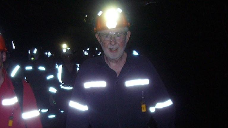 Forskaren och hans följe går i mörker, med hjälmar och pannlampor och arbetskläder med lysande reflexer. Foto: Lena Nordlund/Sveriges Radio