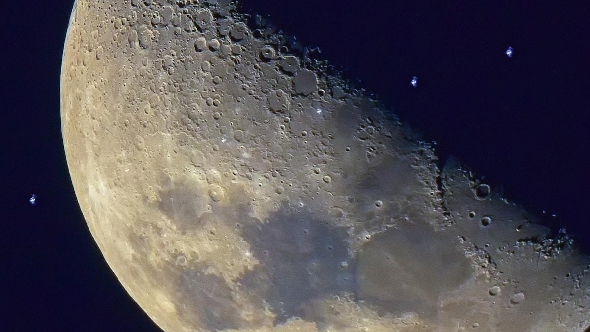 Rymdstationen ISS syns som små lysande prickar med månen som bakgrund.