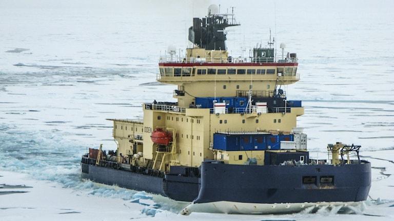 Oden blå och gul stävar genom tunn snöig is