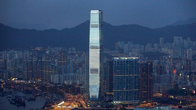 Natt över Hongkongs upplysta skyskrapor som speglar sig i vattnet. Foto: TT