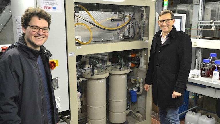 Norbert Martin och Steffen Schneider på företaget JenaBatteries tillsammans med en labbuppställning av ett plastbatteri