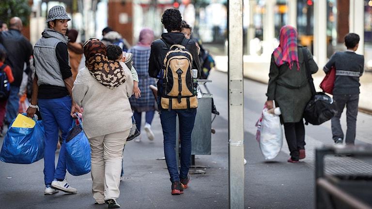 Människor går på rad, med resväskor och ikeakassar, några tittar tillbaka mot kameran. Foto: Anders Wiklund / TT