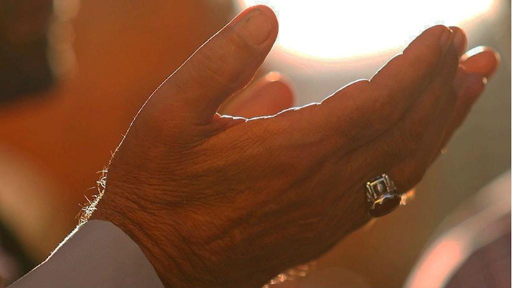 En öppen hand mot himlen under bön.
