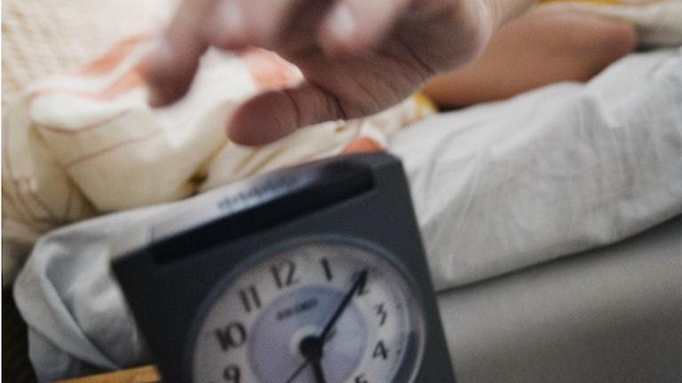 Hand som stänger av väckarklocka.