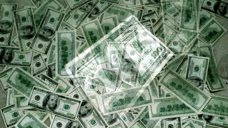 En bild på en hög med 100-dollarsedlar, med en genomskinlig sedel i förgrunden.