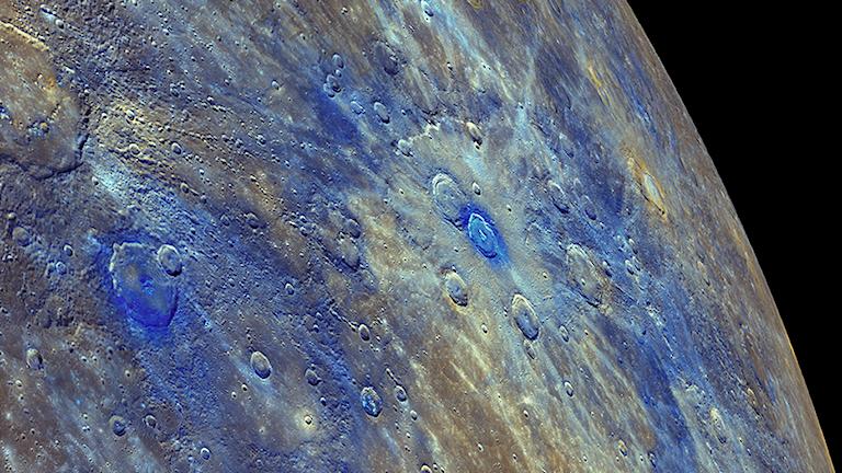 En bild på Merkurius yta. Här färglagd. Ju blåare färg, desto mer kol finns där