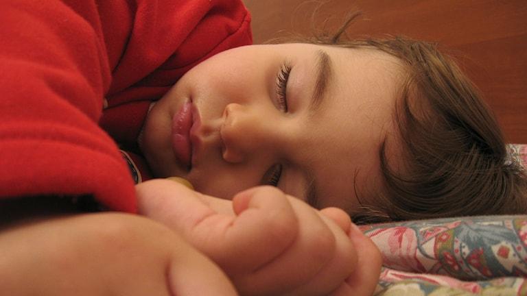 En närbild på ett barn som ligger och sover.