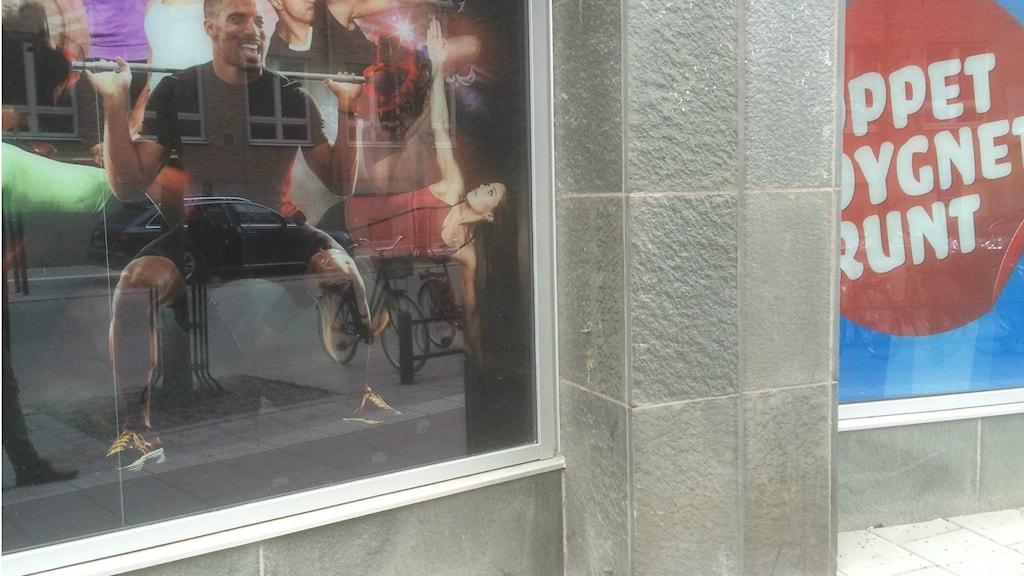 Skyltfönster till gym. Öppet dygnet runt i vit text på röd botten. Bildcollage på glada sportande människor.