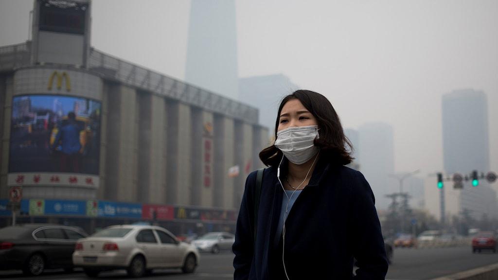 Kvinna med munskydd går på gata i Peking