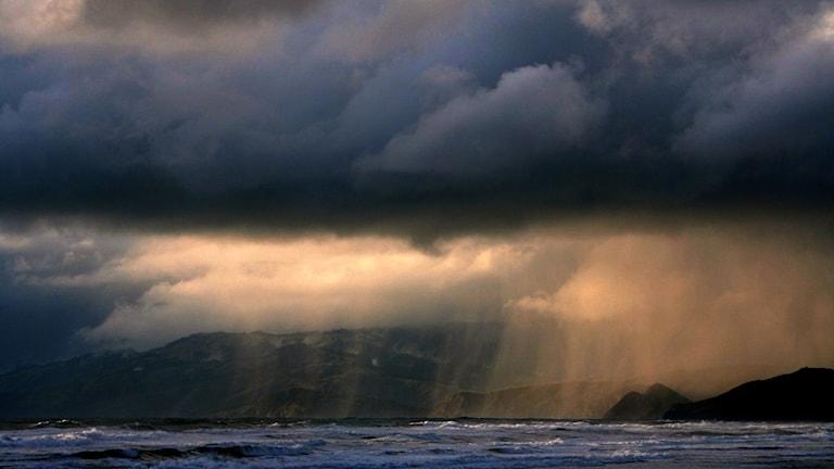 En mörk bild på ett svart regnmoln över vattnet vid en strand. Berg i Bakgrunden.
