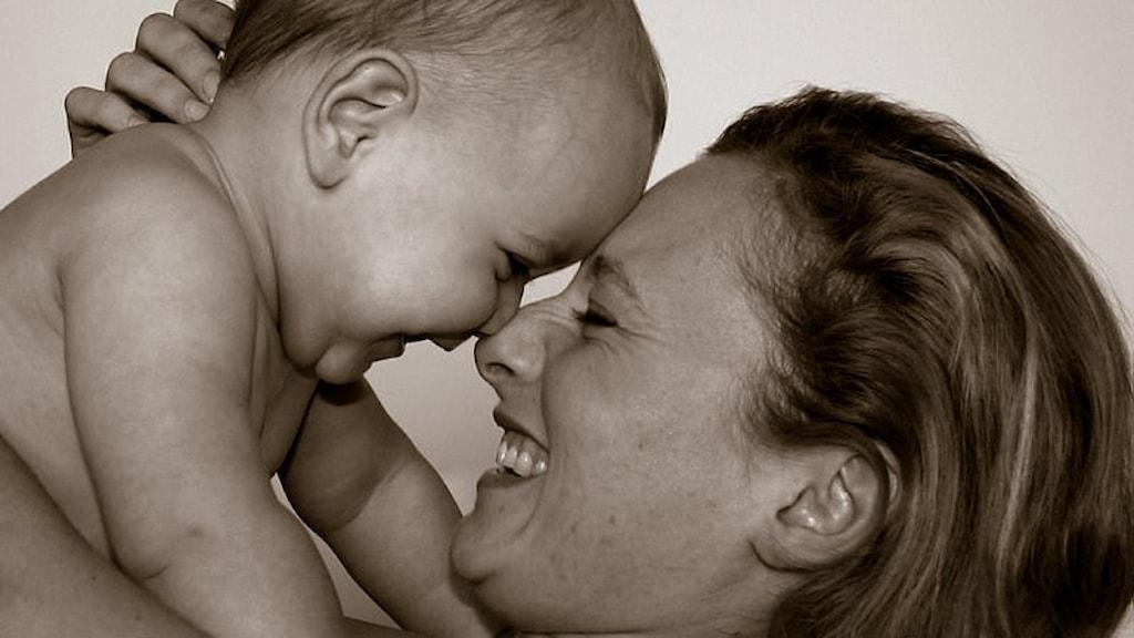 En mamma och en bebis, ansikte mot ansikte. De skrattar.