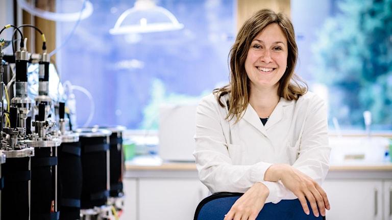 Forskaren Eva-Maria Ekstrand sitter bredvid små biogasreaktorer i forskningslabbet.