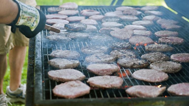 En bild på en stor grill med ungefär 30 hamburgare.