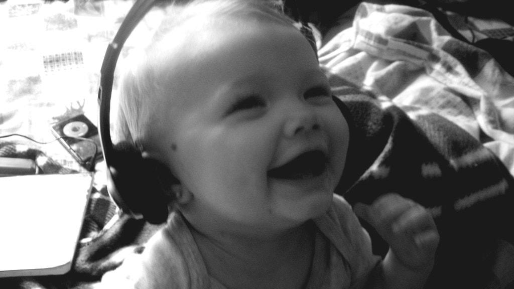 En baby lyssnar på musik i hörlurar
