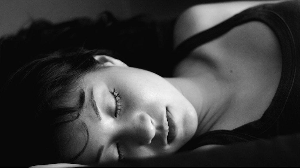 En svartvit närbild på en korthårig kvinna som sover.