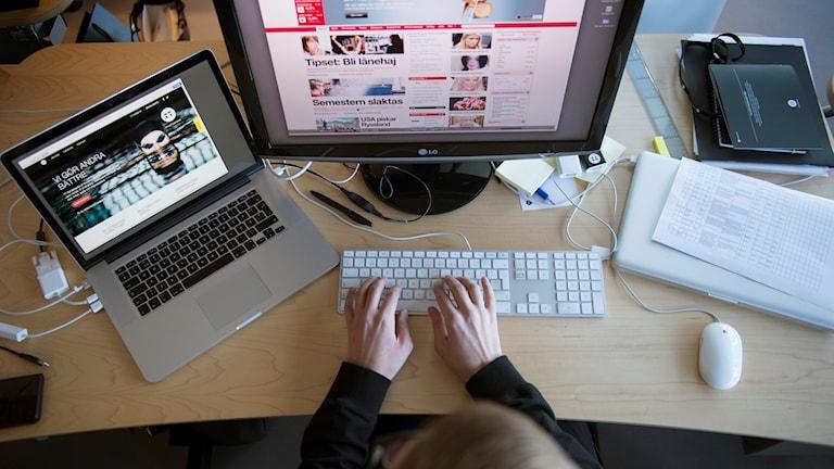 Person uppifrån som sitter vid ett skrivbord med två datorer.