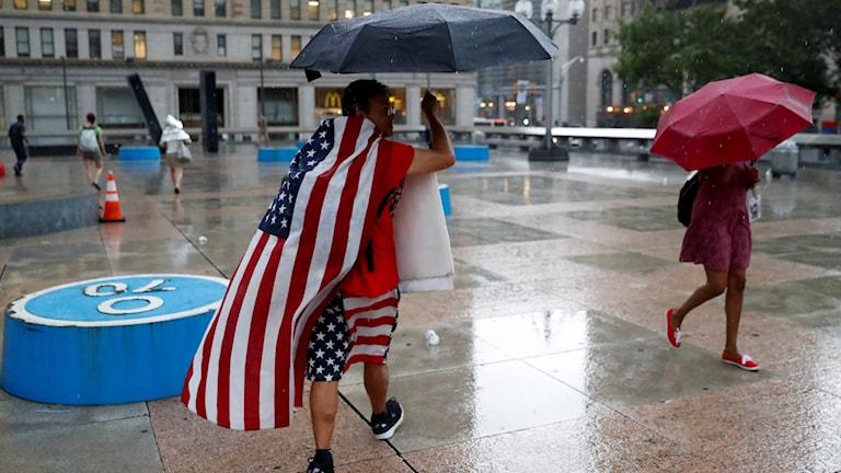 Man i amerikansk flagga går i  regnet