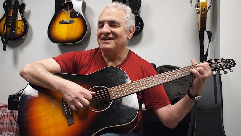 En man spelar på en guitarr blundandes.