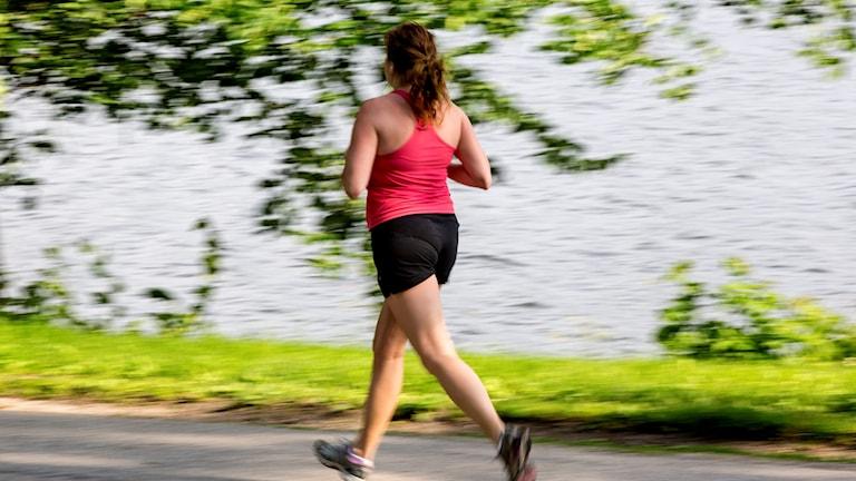 kvinna joggar längs vatten