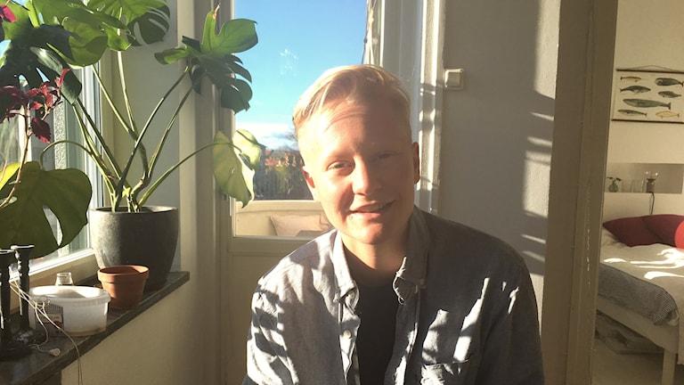 Leo Segelmark, kort blont hår, svart t-shirt, grå skjorta, starkt solljus faller in från vänster, från ett fönster med en grön monstera i grå kruka. Till höger i bakgrunden säng med vita lakan och vinröda kuddar. Fiskplansch ovanför sängen. Rakt bakom Leo, balkongdörr, milsvid utsikt över hus och grönområde. Blå himmel.