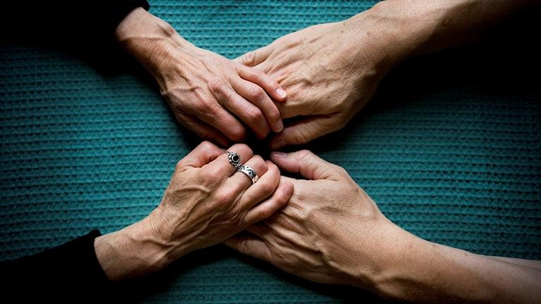 Två par händer som möter varandra och bildar ett kryss mot en turkos bakgrund.