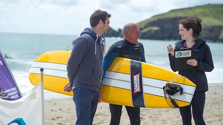 Tre personer på en strand där en är surfare.