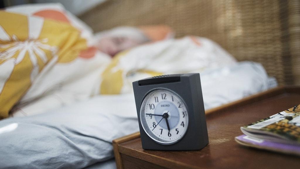 En väckarklocka på ett nattduksbord med sovande person i bakgrunden.