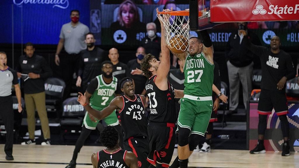 Basketspelare på plan, en hoppar mot korgen med bollen.