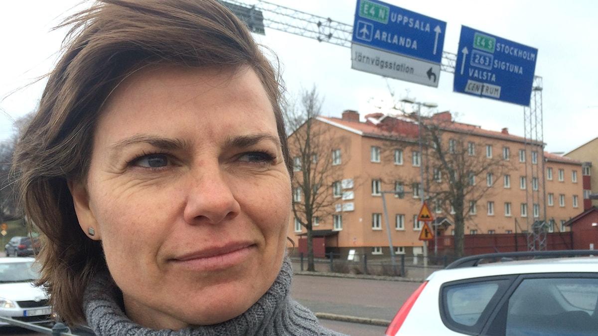 Karin Norström framför vägskylt mot Arlanda