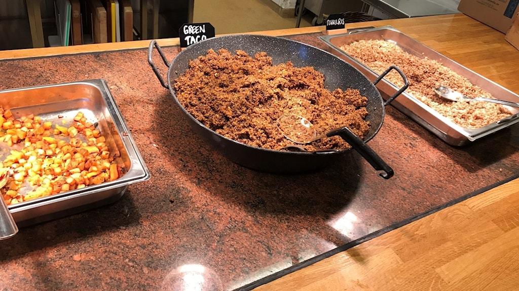 Ett bord med tre matskålar. Mittenskålen är fylld av vegetarisk färs.