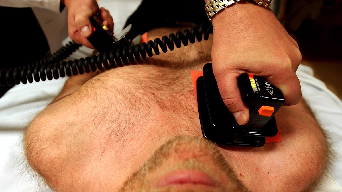 Manlig bar överkropp som behandlas med defibrillatorer.