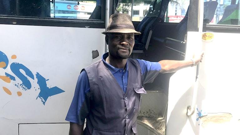 Matthew står med ena handen lutad mot en vit bussdörr.