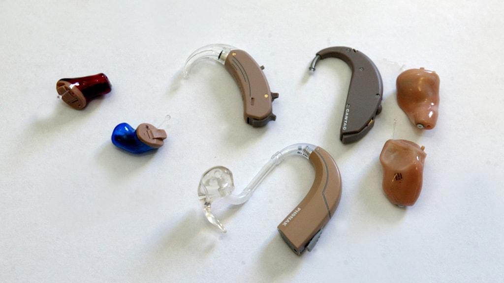 Närbild på sju olika hörapparater, liggandes på ett bord.