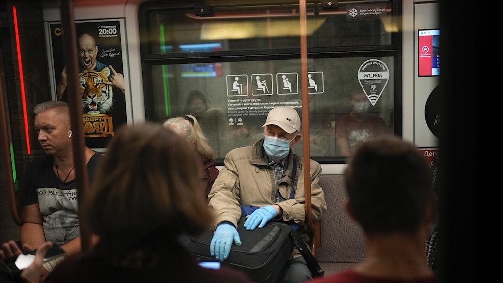 En man med ansiktsmask och handskar som skydd mot coronavirus åker tunnelbana i Moskva, Ryssland.