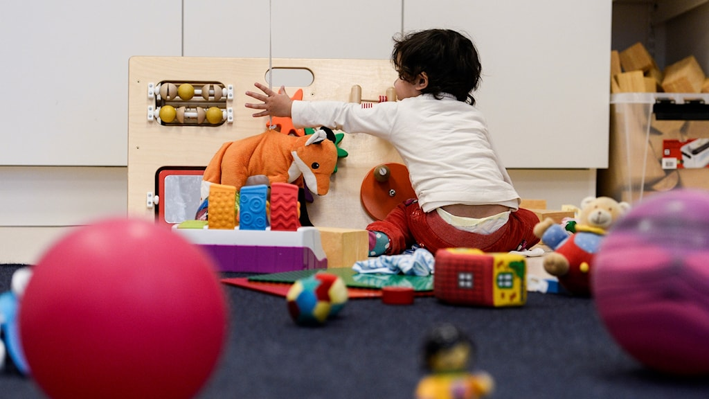 Lekrum med massa leksaker och ett barn i vit tröja och röda byxor som leker.