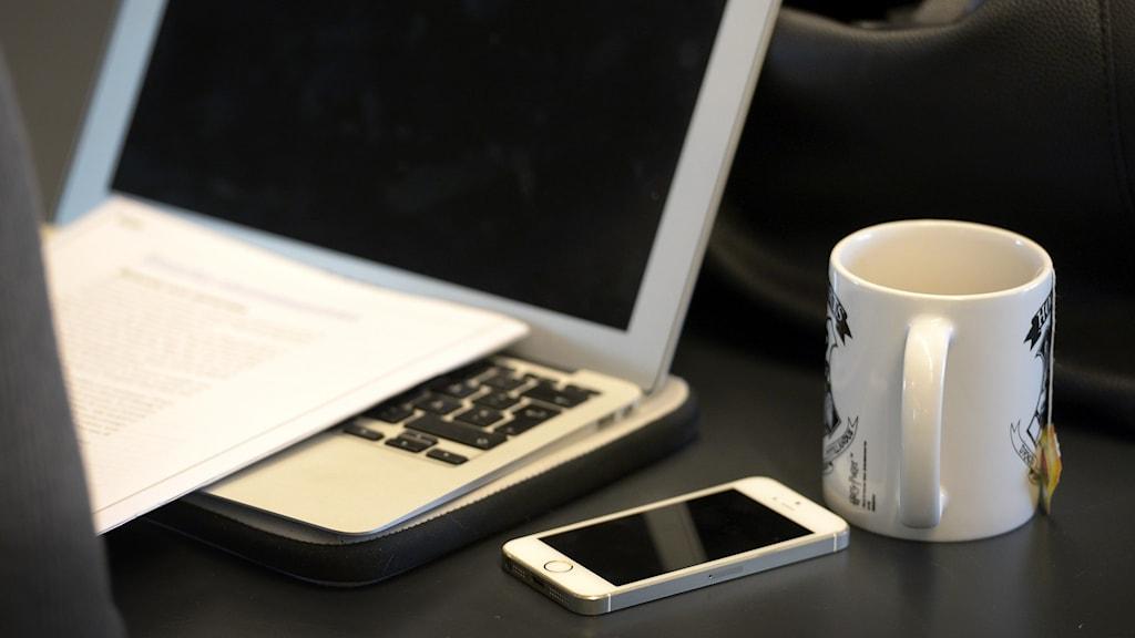 En dator med mörk skärm på ett skrivbord. En tekopp och en telefon bredvid.