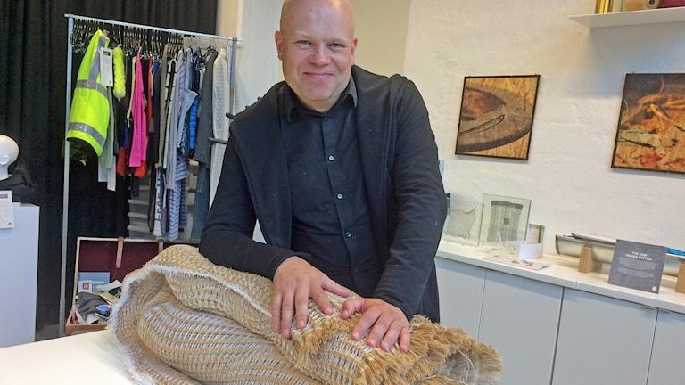 Nils-Krister Persson visar tyget som ser ut som grov säckväv