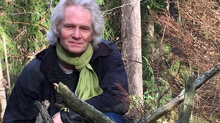 En grå död granstock i förgrunden, liten torr granplanta till höger flankerad av Anders Dahlberg med axellångt grå-blont hår, mörkblå varm jacka och ljusgrön scarf.