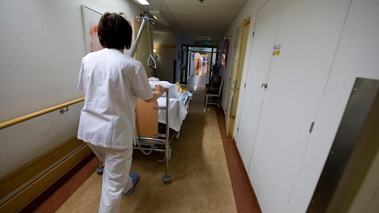 Vårdpersonal flyttar på en patient på en vårdavdelning