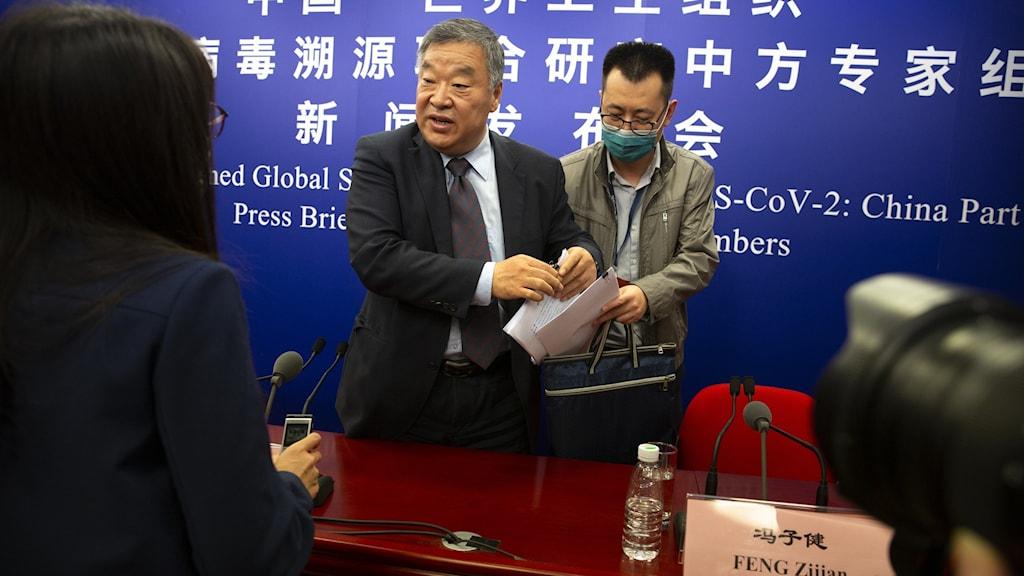 En man står och pratar och har en assistent bakom sig som håller i papper. På väggen kinesiska tecken.