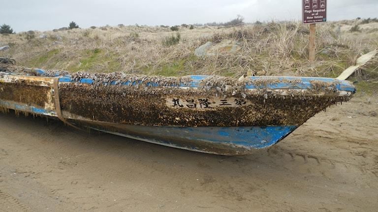 En japansk båt ligger på en strand.