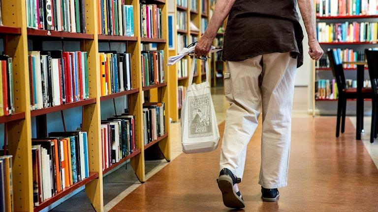 Baksida på kvinna gående i ett bibliotek