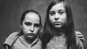 Två tjejer i 7 till 9 år håller om varandra och ser hårda ut.
