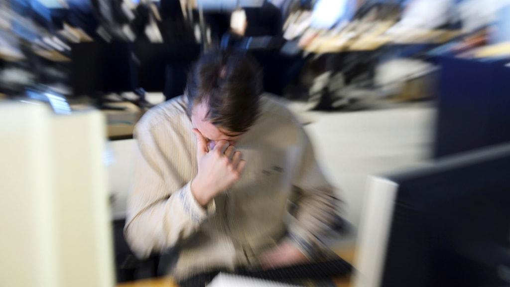 En stressad man sitter vid sin arbetsplats och håller handen för ögonen.