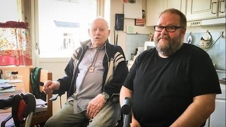 Två män, den ena i 90-årsålder och den andra yngre, sitter i ett kök.