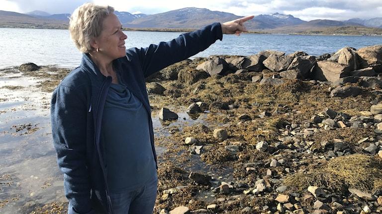 Blond kvinna i luddig tröja på stenig strand pekar mot in mot bilden.