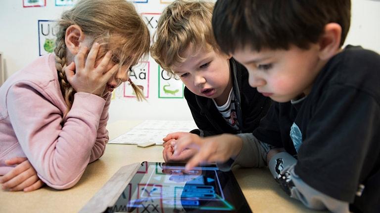 Tre barn vid en datorplatta