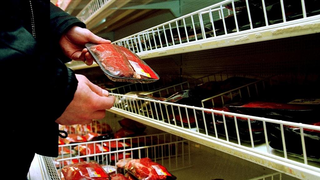 En person tar ett köttråg från en butikshylla.