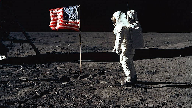 Astronaut och de amerikanska flaggan på månen.