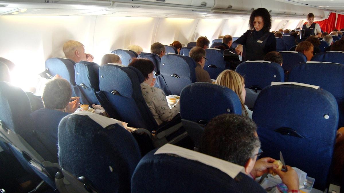 flygvärdinna serverar passagerare.